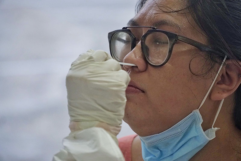 Bác sĩ tiến hành lấy mẫu dịch mũi để làm xét nghiệm